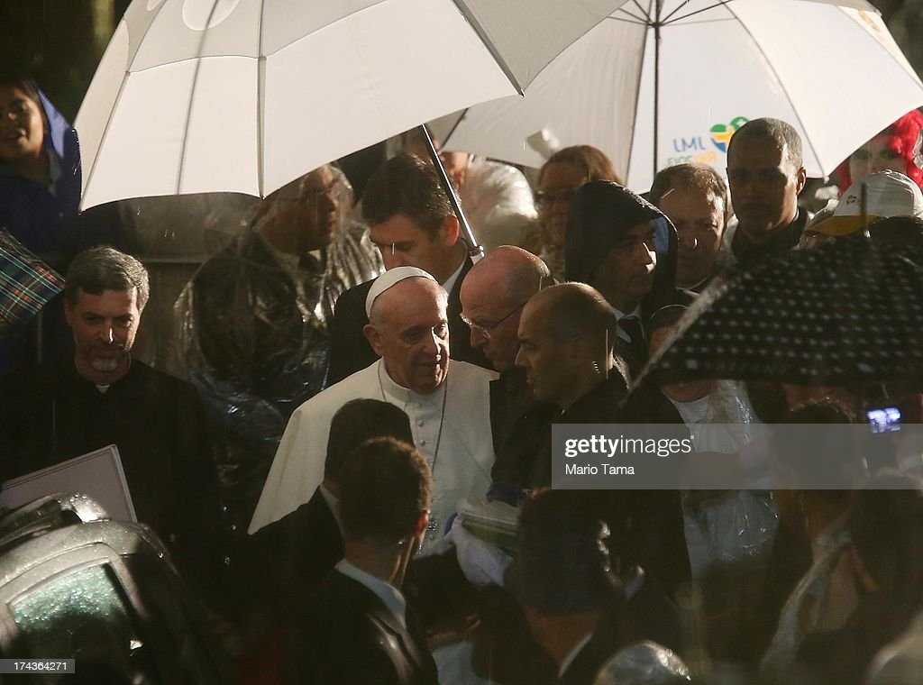 <a gi-track='captionPersonalityLinkClicked' href=/galleries/search?phrase=Pope+Francis&family=editorial&specificpeople=2499404 ng-click='$event.stopPropagation()'>Pope Francis</a> (Center L) departs in the rain after speaking at the Hospital de Sao Francisco de Assis (Hospital of Saint Francis of Assisi) on July 24, 2013 in Rio de Janeiro, Brazil. More than 1.5 million pilgrims are expected to join <a gi-track='captionPersonalityLinkClicked' href=/galleries/search?phrase=Pope+Francis&family=editorial&specificpeople=2499404 ng-click='$event.stopPropagation()'>Pope Francis</a> for his visit to the Catholic Church's World Youth Day celebrations. <a gi-track='captionPersonalityLinkClicked' href=/galleries/search?phrase=Pope+Francis&family=editorial&specificpeople=2499404 ng-click='$event.stopPropagation()'>Pope Francis</a> will deliver his welcome address to the celebrations on Copacabana Beach on July 25 as World Youth Day runs July 23-28.