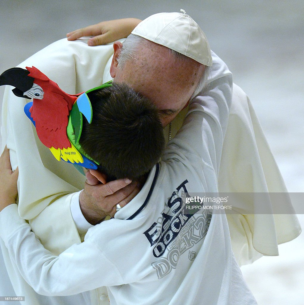 Pope Francis embraces a child as he arrives in the Paul VI hall prior to his meeting with the Italian Union for the transportation of sick people to Lourdes and International Shrines (UNITALSI) on November 9, 2013 at the Vatican.
