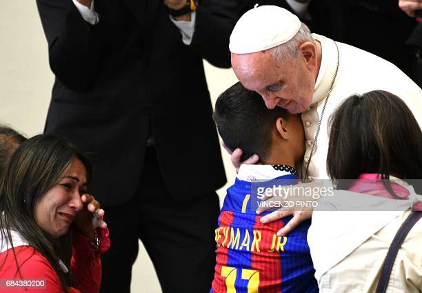 TOPSHOT Pope Francis embraces a young member of the congregation after an audience for Huntingtons disease sufferers and their families on May 18...