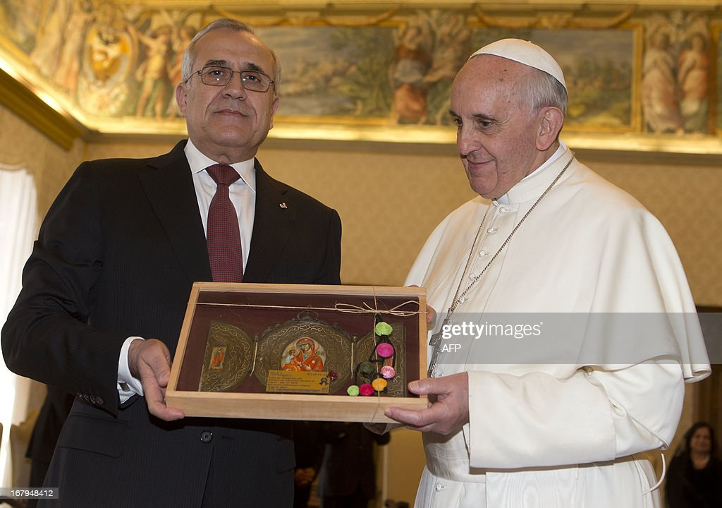 Pope Francis (R) exchange gifts with Lebanese President Michel Suleiman during a private audience in the pontiff's library at the Vatican on May 3, 2013.