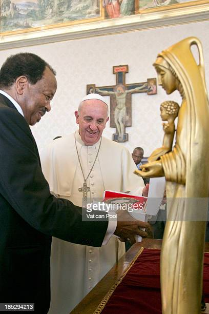 Pope Francis exchanges gifts with Cameroon President Paul Biya during an audience at Vatican Apostolic Palace on October 18 2013 in Vatican City...