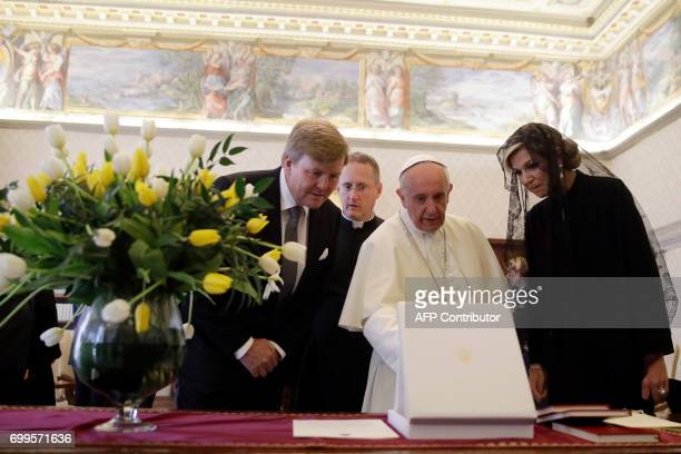 Pope Francis exchanges gifts with Dutch King WillemAlexander and Queen Maxima during a private audience at the Vatican on June 22 2017 / AFP PHOTO /...