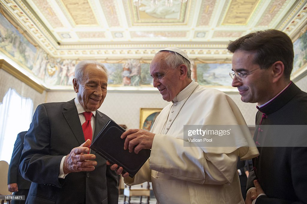 Pope Francis (C) exchanges gifts with Israeli president <a gi-track='captionPersonalityLinkClicked' href=/galleries/search?phrase=Shimon+Peres&family=editorial&specificpeople=201775 ng-click='$event.stopPropagation()'>Shimon Peres</a> (L) during an audience at his private library on April 30, 2013 in Vatican City, Vatican. The Pontiff and President <a gi-track='captionPersonalityLinkClicked' href=/galleries/search?phrase=Shimon+Peres&family=editorial&specificpeople=201775 ng-click='$event.stopPropagation()'>Shimon Peres</a> debated on a variety of issues concerning the Middle East during their meeting.