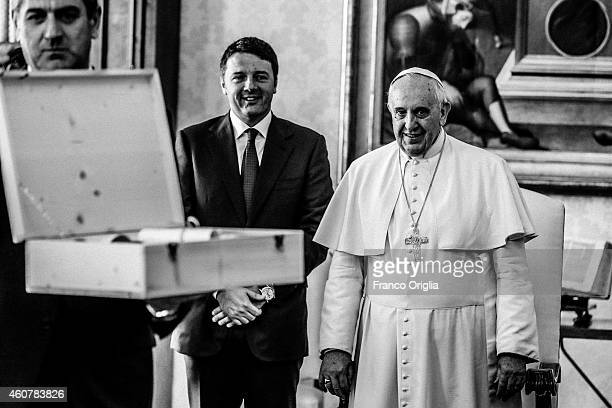 Pope Francis exchanges gifts with Italian Prime Minister Matteo Renzi at his private library in the Apostolic Palace on December 13 2014 in Vatican...
