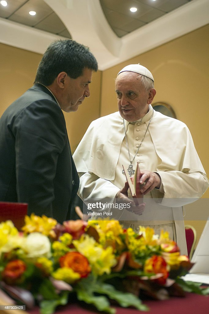 Pope Francis exchanges gifts with President of Paraguay Horacio Manuel Cartes Jara during an audience at the Paul VI Hall on April 29, 2014 in Vatican City, Vatican. In his homily at morning mass in Casa Santa Marta Tuesday, Pope Francis focused on 'the three characteristics' of this group, capable of full agreement inside the community, to bear witness of Christ to the outside world, to prevent any of its members from suffering and misery.