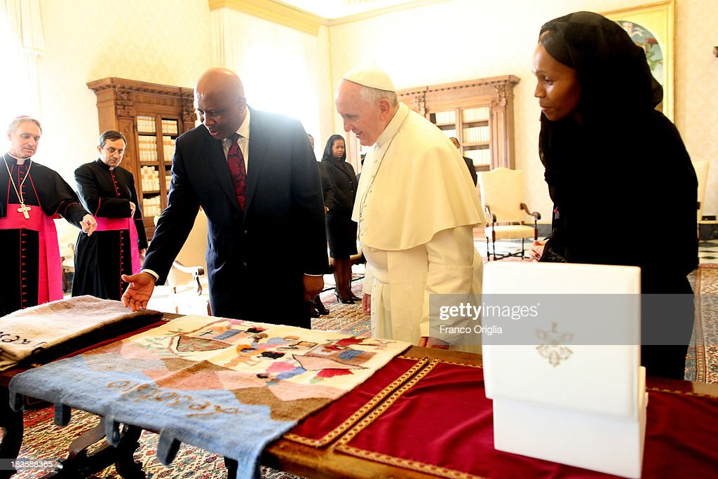 Pope Francis (C) exchanges gifts with the King of Lesotho Letsie III (L) and the Queen Masenate Mohato Seeiso (R) during an audience on October 7, 2013 in Vatican City, Vatican. The themes of their meeting have been education, family and religious freedom.
