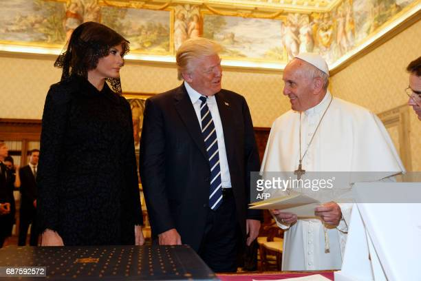 Pope Francis exchanges gifts with US President Donald Trump and US First Lady Melania Trump during a private audience at the Vatican on May 24 2017...