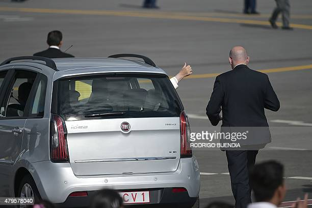 Pope Francis extends his hand out of the window as he leaves aboard a small car the Mariscal Sucre international airport in Quito on July 5 2015 Pope...