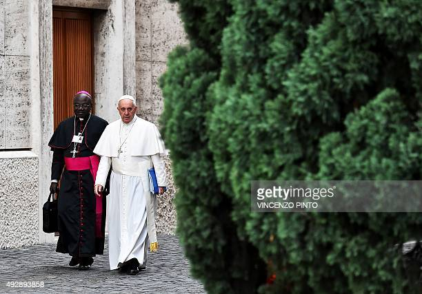 Pope Francis flanked by a bishop arrives at the Paul VI hall to preside the Synod on the family at the Vatican on October 16 2015 AFP PHOTO /...