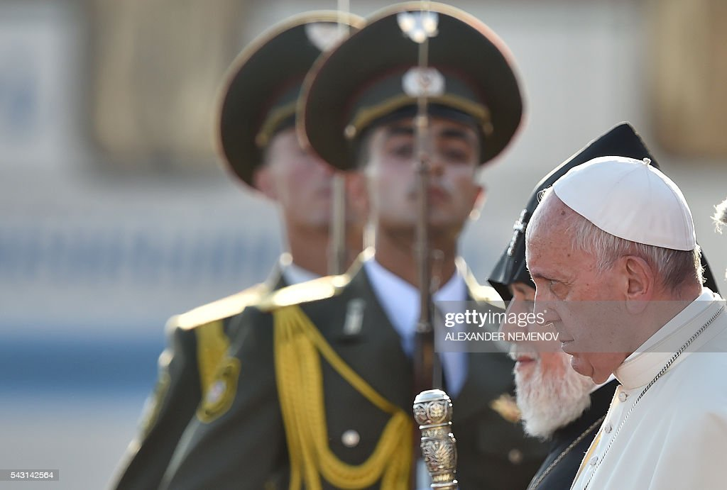 Pope Francis, flanked by Catholicos of All Armenians Karekin II, walks past honour guards to board a plane for Rome at Yerevan's Zvartnots Airport on June 26, 2016. / AFP / ALEXANDER