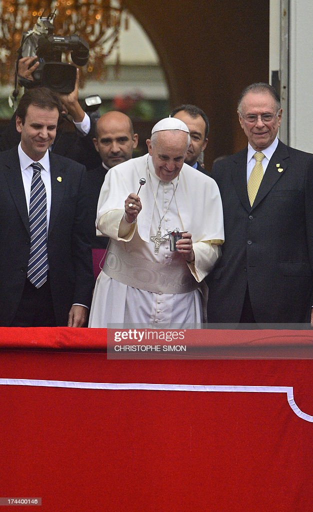 Pope Francis (C), flanked by the president of the Brazilian Olympic Committee, Carlos Arthur Nuzman (R) and Rio's Mayor Eduardo Paes (L), blesses the crowd during a ceremony at the City Palace in Rio de Janeiro where he arrived to receive the keys of the city and bless the Olympic flags ahead of the Rio 2016 Summer Games, on July 25, 2013. The first Latin American and Jesuit pontiff arrived in Brazil mainly for the huge five-day Catholic gathering World Youth Day.