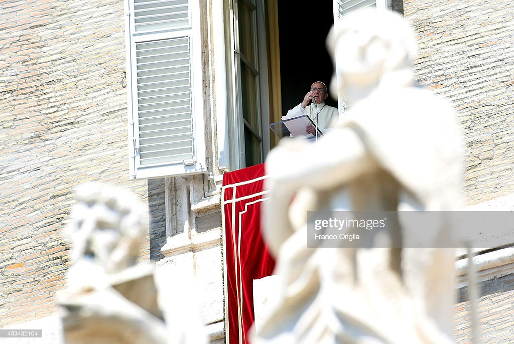 Pope Francis, framed by sculptures of St Peter's colonnade, delivers his Angelus blessing from the window of the former Papal apartments on August 10, 2014 in Vatican City, Vatican. Pope Francis renewed his call for prayer and assistance for those suffering in Iraq. He also prayed for an end to the fighting between Israeli forces and Hamas militants in Gaza, as well as for the victims of the Ebola virus. Pope Francis will visit South Korea from August 14 to August 18.