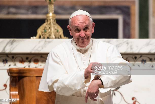 Pope Francis gestures to his watch to apologize for not being able to greet everyone at the end of a midday prayer with US bishops at the Cathedral...