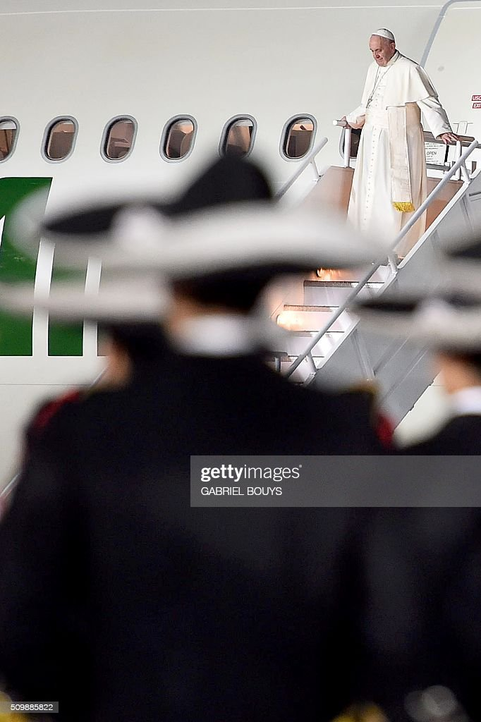 Pope Francis gets off his plane upon his arrival at Benito Juarez international airport in Mexico City on February 12, 2016. Catholic faithful flocked to the streets of Mexico City to greet Pope Francis on Friday after the pontiff held a historic meeting with the head of the Russian Orthodox Church in Cuba. AFP PHOTO/GABRIEL BOUYS / AFP / GABRIEL BOUYS