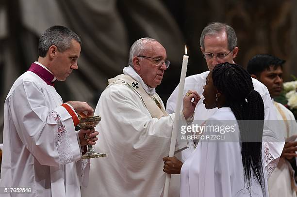 Pope Francis gives the holy communion during the Easter Vigil at the St Peter's basilica on March 26 2016 in Vatican Christians around the world are...