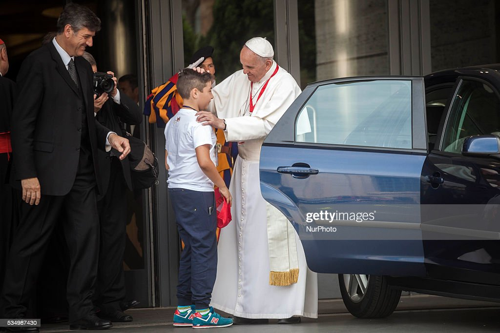 """Pope Francis greets a boy as he leaves at the end of a meeting with 400 children coming by train from the region of Calabria in Vatican City, Vatican on May 28, 2016. """"Brought by waves is the slogan of the fourth edition of the """"Childrens Train"""", an initiative of the Pontifical Council for Culture. In collaboration with Italian State Railways, four hundred children from schools in Italys southern region of Calabria make the long trip to the Vatican to meet Pope Francis."""