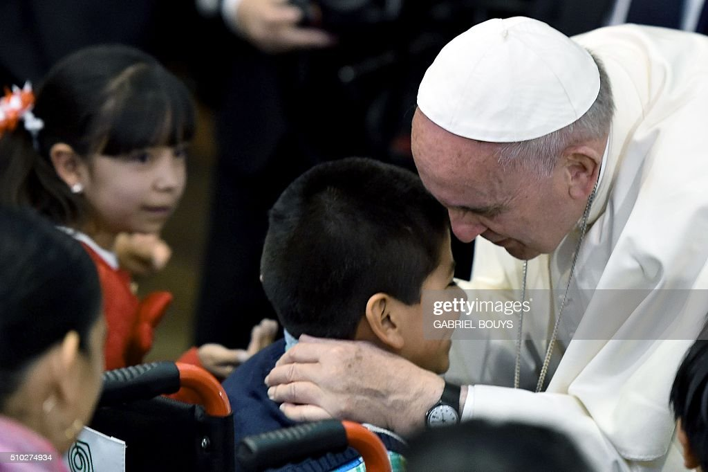 Pope Francis greets a child during his visit to the Federico Gómez Children's Hospital in Mexico City on February 14, 2016. The pope is in Mexico for a trip encompassing two of the defining themes of his papacy: bridge-building diplomacy and his concern for migrants seeking a better life. AFP PHOTO / GABRIEL BOUYS / AFP / GABRIEL BOUYS