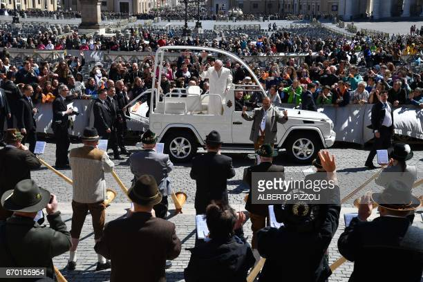Pope Francis greets a group of German Alpenhorn players from the popemobile at the end of a weekly general audience at St Peter's square on April 19...