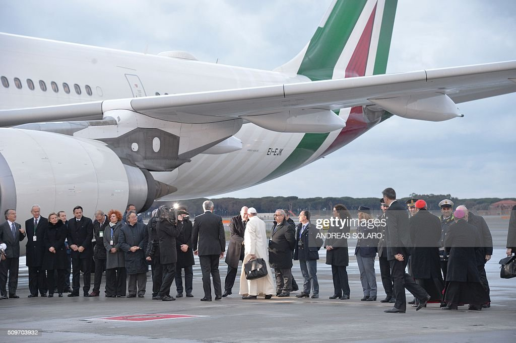 Pope Francis (C) greets as he boards a plane to Cuba for a historic meeting with Russian Patriarch Kirill before his trip to Mexico for a five-day visit, on February 12, 2016 at Fiumicino airport, near Rome. / AFP / ANDREAS SOLARO
