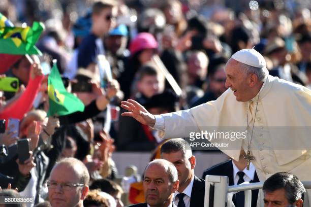 Pope Francis greets faithful as he arrives for his weekly general audience in St Peter's square on October 11 2017 at the Vatican / AFP PHOTO /...