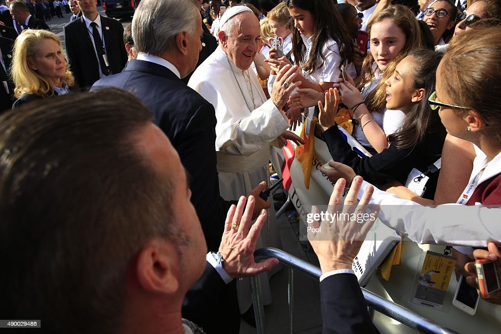 Pope Francis greets guests upon his arrival at Our Lady Queen of Angels School on September 25, 2015 in the East Harlem neighborhood of New York City. Pope Francis is on a six-day trip to the USA, which includes stops in Washington DC, New York and Philadelphia, after a three-day stay in Cuba.