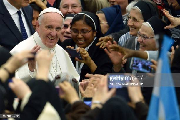 TOPSHOT Pope Francis greets nuns as he arrives for a meeting with religious for the conclusion of the Year of Consecrated Life at Paul VI audience...