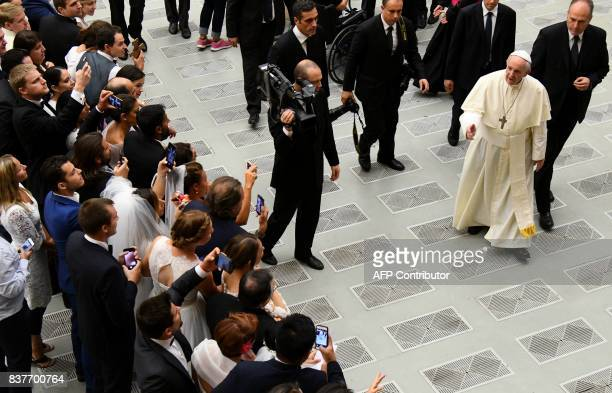 Pope Francis greets people at the Paul VI hall at the Vatican at the end of his weekly general audience on August 23 2017 / AFP PHOTO / VINCENZO PINTO
