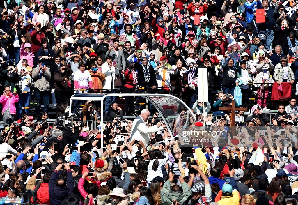 Pope Francis greets people on his ride in the popemobile to the Zocalo in Mexico City on February 13, 2016. AFP PHOTO/ Mario Vázque / AFP / MARIO VAZQUEZ