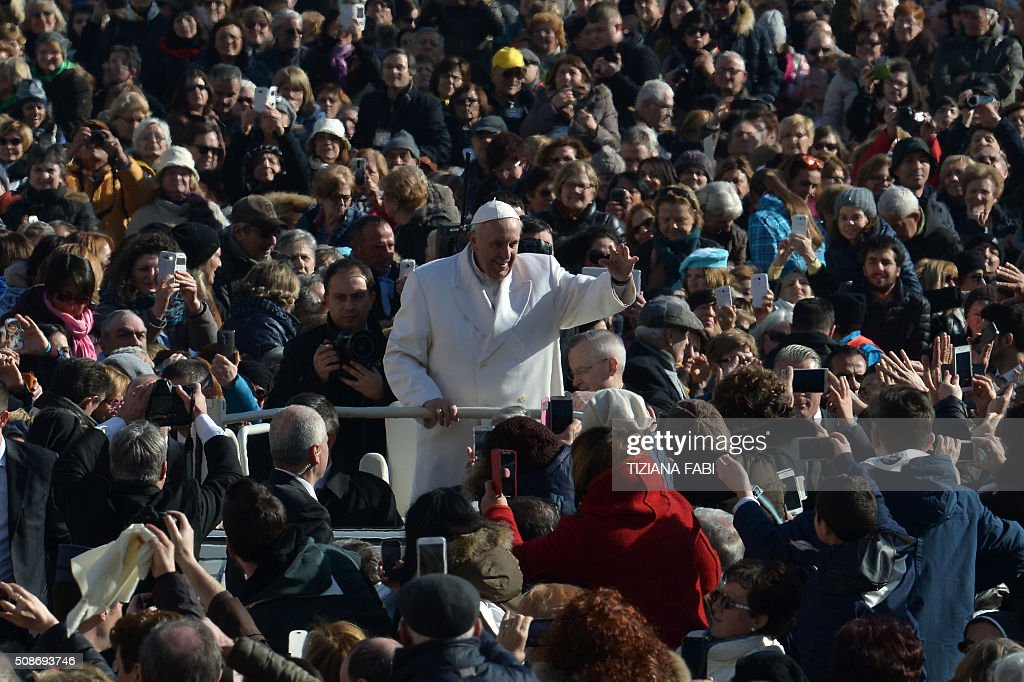 Pope Francis greets the crowd as he arrives for an audience to the Padre Pio Prayer Groups, on February 6, 2016 in Vatican. Pio was revered during his lifetime (1887-1968) and his popularity has continued to grow since his death, particularly in Italy, where mini-statues and pictures of the mystical Capuchin friar are ubiquitous. / AFP / TIZIANA FABI
