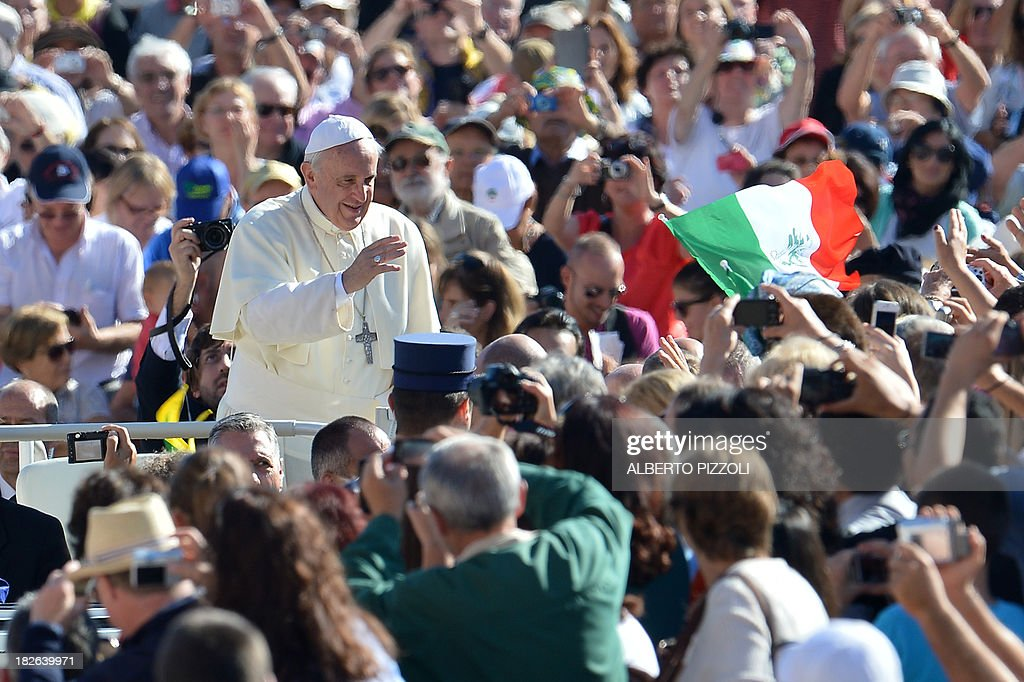 Pope Francis greets the crowd as he arrives for his general audience at St Peter's square on September 25, 2013 at the Vatican. AFP PHOTO / ALBERTO PIZZOLI
