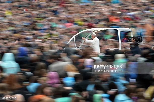 Pope Francis greets the crowd from the popemobile after the Easter Mass on April 5 2015 in Vatican Pope Francis condemned yesterday indifference and...