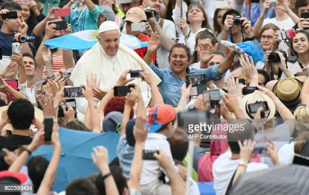 Pope Francis greets the crowd from the popemobile as he arrives for a weekly general audience at St Peter's square on June 28 2017 in Vatican / AFP...