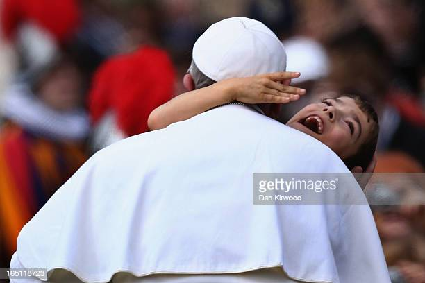 Pope Francis holds a disabled child as he greets the faithful prior to his first 'Urbi et Orbi' blessing from the balcony of St Peter's Basilica...