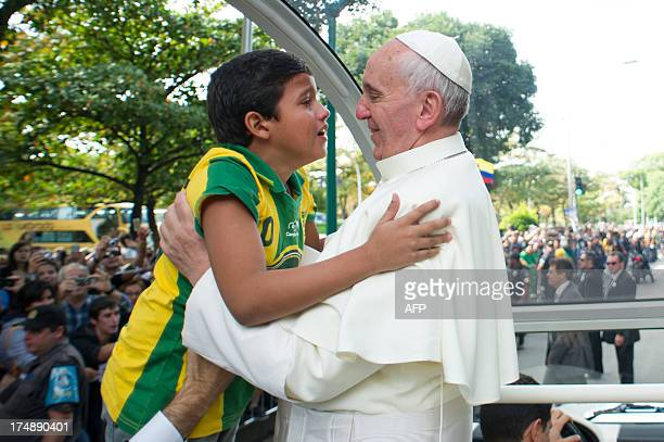 Pope Francis hugs a boy at Quinta da Boa Vista Park in Rio de Janeiro Brazil on July 26 2013 Pope Francis returned to Rome late Sunday after leading...
