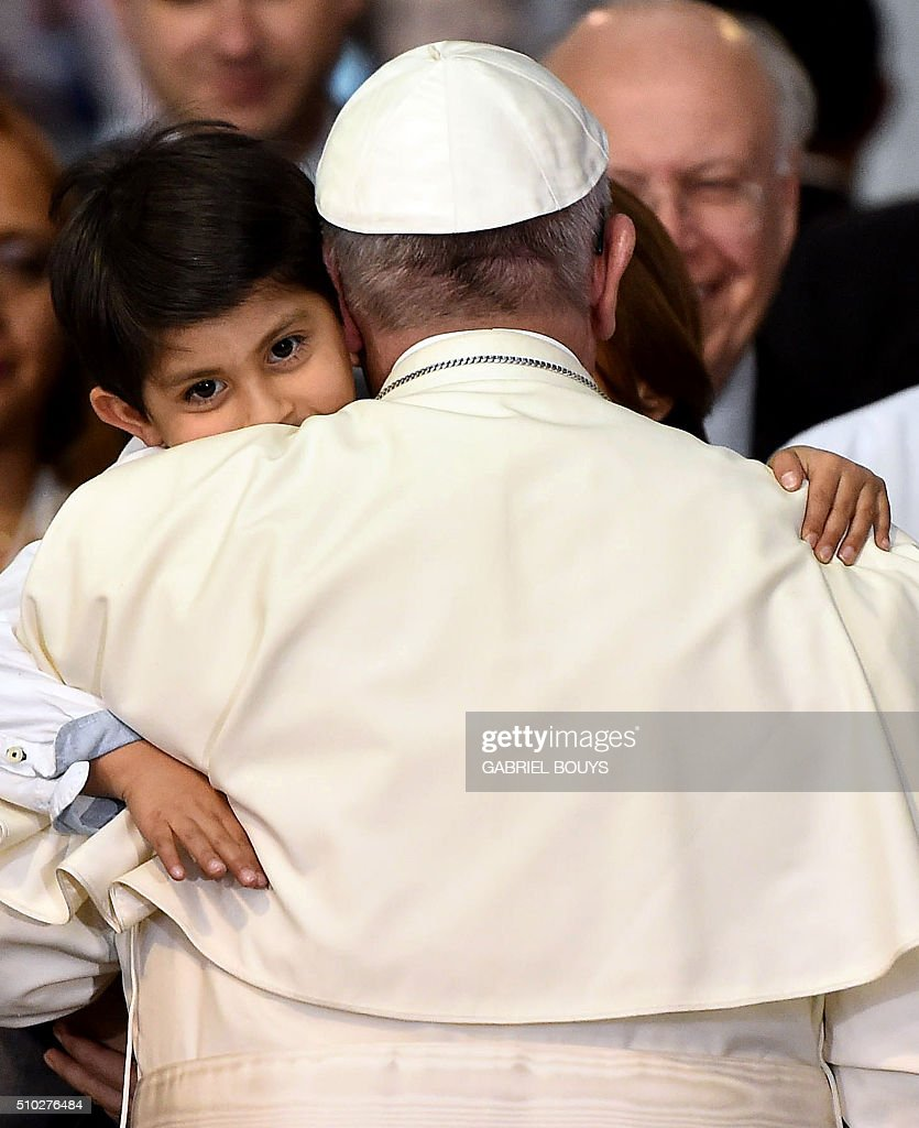 Pope Francis hugs a child during his visit to the Federico Gómez children's hospital in Mexico on February 14, 2016. Pope Francis celebrated an open-air mass with 300,000 Catholic faithful in a crime-plagued Mexican city on Sunday, urging them to create a country free of emigration and 'merchants of death.' The inscription in the sketch reads 'Welcome!!! Dear Pope'. AFP PHOTO / GABRIEL BOUYS / AFP / GABRIEL BOUYS