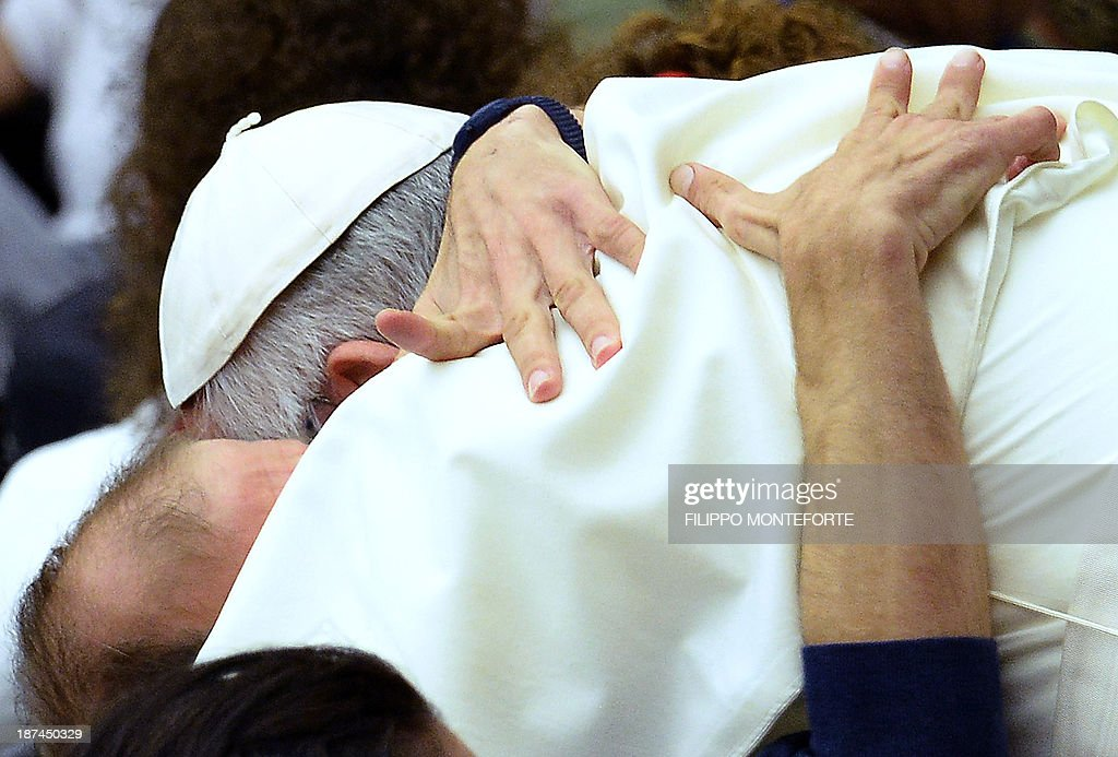 Pope Francis hugs a disabled man during a meeting with the UNITALSI, the Italian Union responsible for the transportation of sick people to Lourdes and the International Shrines in PaulVI hall, at the Vatican, on November 9, 2013.