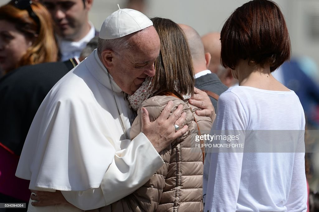 Pope Francis hugs a woman at the end of his weekly general audience at St Peter's square on May 25, 2016 in Vatican. / AFP / Filippo MONTEFORTE
