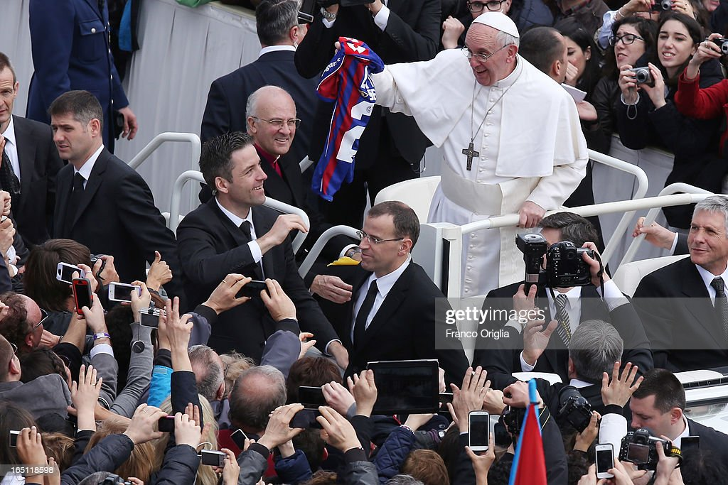 <a gi-track='captionPersonalityLinkClicked' href=/galleries/search?phrase=Pope+Francis&family=editorial&specificpeople=2499404 ng-click='$event.stopPropagation()'>Pope Francis</a> is given a football shirt as he greets the faithful prior to his first 'Urbi et Orbi' blessing from the balcony of St. Peter's Basilica during Easter Mass on March 31, 2013 in Vatican City, Vatican. <a gi-track='captionPersonalityLinkClicked' href=/galleries/search?phrase=Pope+Francis&family=editorial&specificpeople=2499404 ng-click='$event.stopPropagation()'>Pope Francis</a> delivered his message to the gathered faithful from the central balcony of St. Peter's Basilica in St. Peter's Square after his first Holy week as Pontiff.