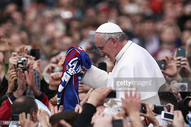Pope Francis is given a San Lorenzo's shirt the Buenos Aires football team as he greets the faithful prior to his first 'Urbi et Orbi' blessing from...