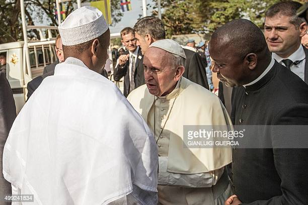 Pope Francis is greet by Central Mosque Imam Nehedid Tidjani upon his arrival in the PK5 neighborhood on November 30 2015 in Bangui Pope Francis on...