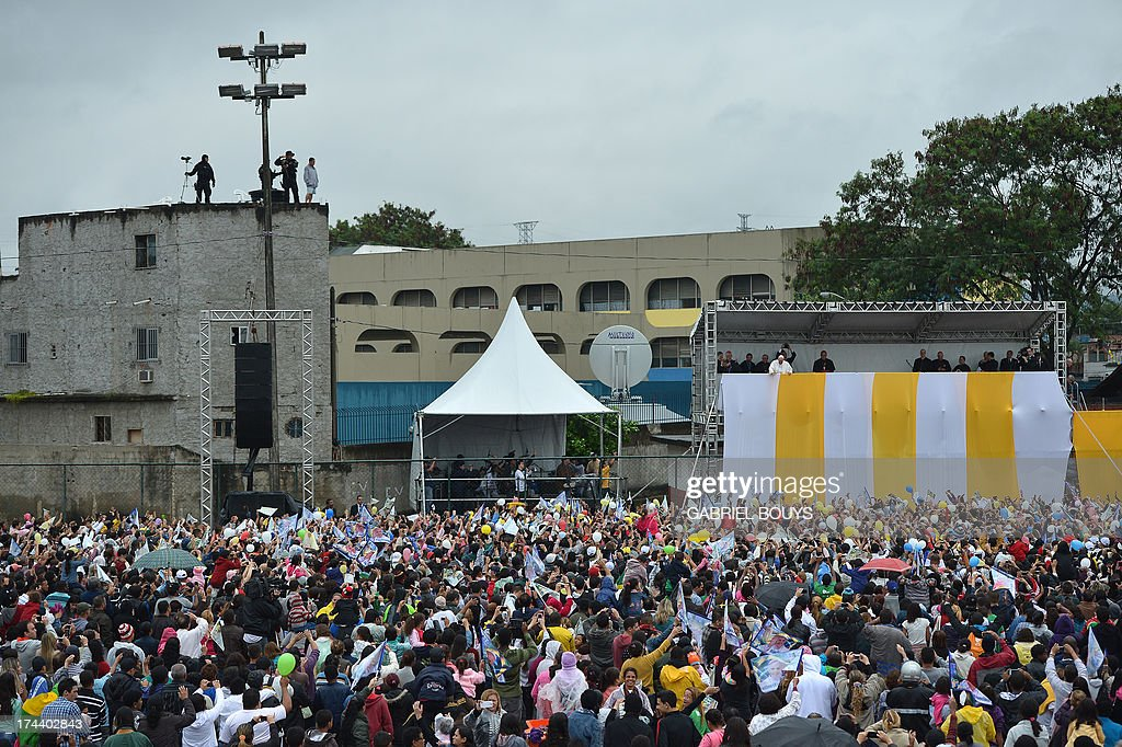 Pope Francis is greeted by a crowd as he appears on a stand during his visit to the Varginha favela in Rio de Janeiro, on July 25, 2013. The Varginha favela is a community of 1,000 people which for decades was under the sway of narco-traffickers until it came under police control less than a year ago. The first Latin American and Jesuit pontiff arrived in Brazil mainly for the huge five-day Catholic gathering World Youth Day.