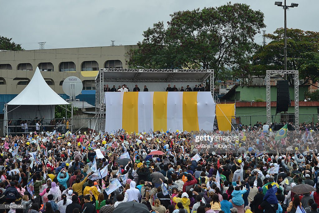 Pope Francis is greeted by a crowd as he appears on a stand mounted on a football field during his visit to the Varginha favela in Rio de Janeiro, on July 25, 2013. The Varginha favela is a community of 1,000 people which for decades was under the sway of narco-traffickers until it came under police control less than a year ago. The first Latin American and Jesuit pontiff arrived in Brazil mainly for the huge five-day Catholic gathering World Youth Day.