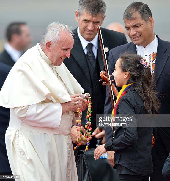 Pope Francis is greeted by a girl as Ecuadorean President Rafael Correa looks on at the airport in Quito before his departure for Bolivia on July 8...