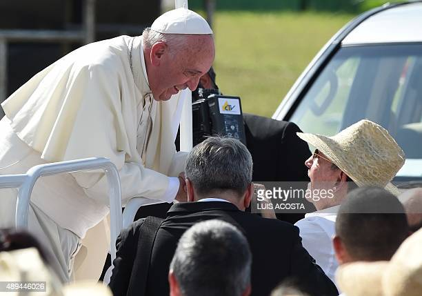 Pope Francis is greeted by Cuban President Raul Castro as he arrives to give a morning mass at the Calixto Garcia square in Holguin in eastern Cuba...