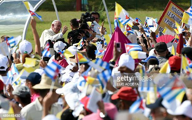 Pope Francis is greeted by the crowd as he arrives to give a morning mass at the Calixto Garcia square in Holguin in eastern Cuba on September 21...