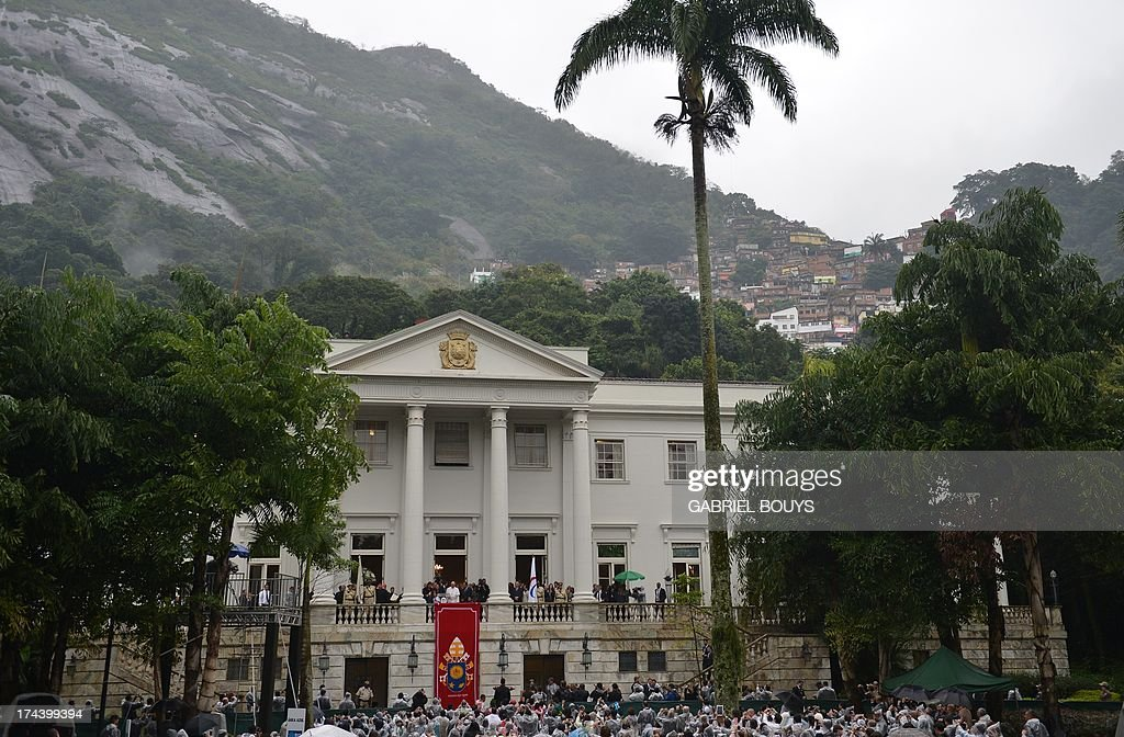 Pope Francis (C in white on balcony) is pictured at the City Palace in Rio de Janeiro where he will receive the keys of the city and bless the Olympic flags ahead of the Rio 2016 Summer Games, on July 25, 2013. The first Latin American and Jesuit pontiff arrived in Brazil mainly for the huge five-day Catholic gathering World Youth Day. AFP PHOTO / GABRIEL BOUYS