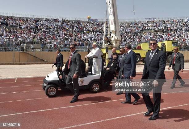 Pope Francis is surrounded by security as he rides an uncovered Popemobile before the start of a mass on April 29 2017 at a stadium in Cairo Pope...