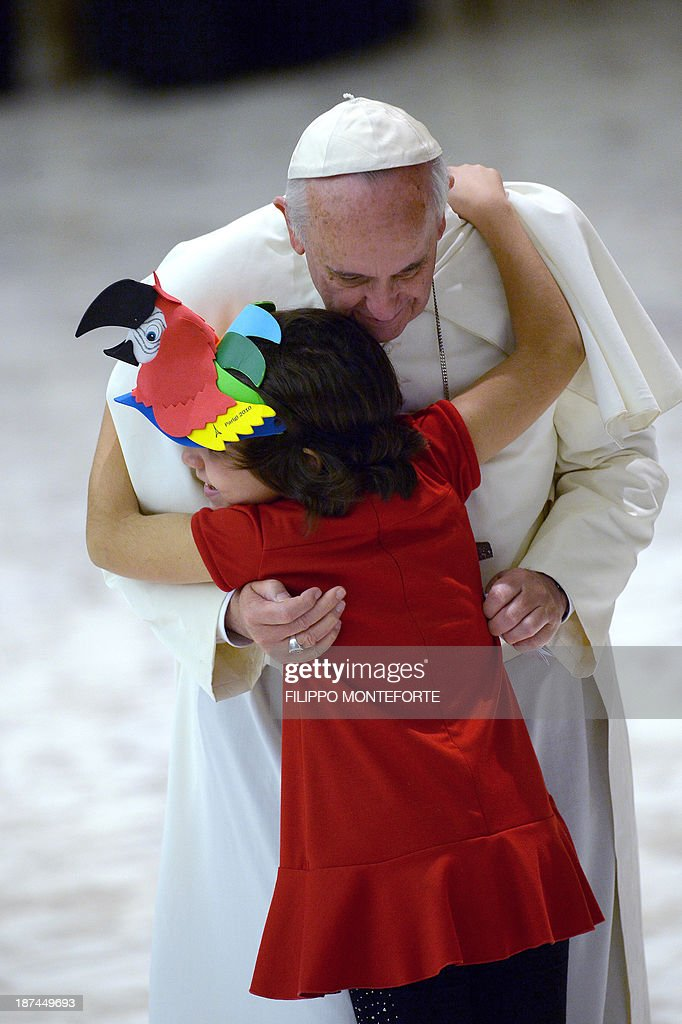 Pope Francis is welcomed by a child as he arrives in the Paul VI hall prior to his meeting with the Italian Union for the transportation of sick people to Lourdes and International Shrines (UNITALSI) on November 9, 2013 at the Vatican.