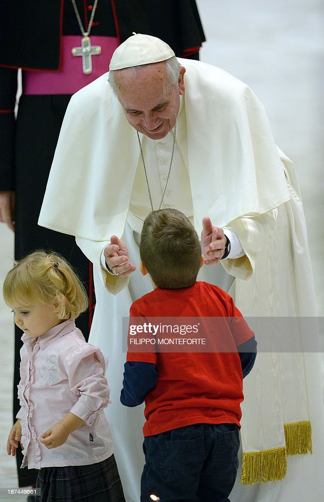 Pope Francis is welcomed by children as he arrives in the Paul VI hall prior to his meeting with the Italian Union for the transportation of sick people to Lourdes and International Shrines (UNITALSI) on November 9, 2013 at the Vatican.