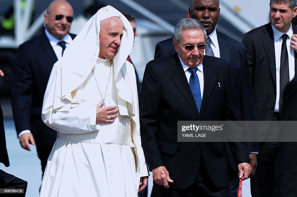 Pope Francis (L) is welcomed by Cuban President Raul Castro at the International Airport Jose Marti in Havana, on February 12, 2016. Pope Francis landed in Cuba Friday to meet with the head of the Russian Orthodox Church, the first such encounter since the two branches of Christianity split a millennium ago. The 79-year-old pontiff, in his white robes, stepped off an Alitalia plane and shook hands with Cuban President Raul Castro on the tarmac at Jose Marti airport, where he was then due to sit down with the Russian Patriarch Kirill. AFP PHOTO / YAMIL LAGE / AFP / YAMIL LAGE